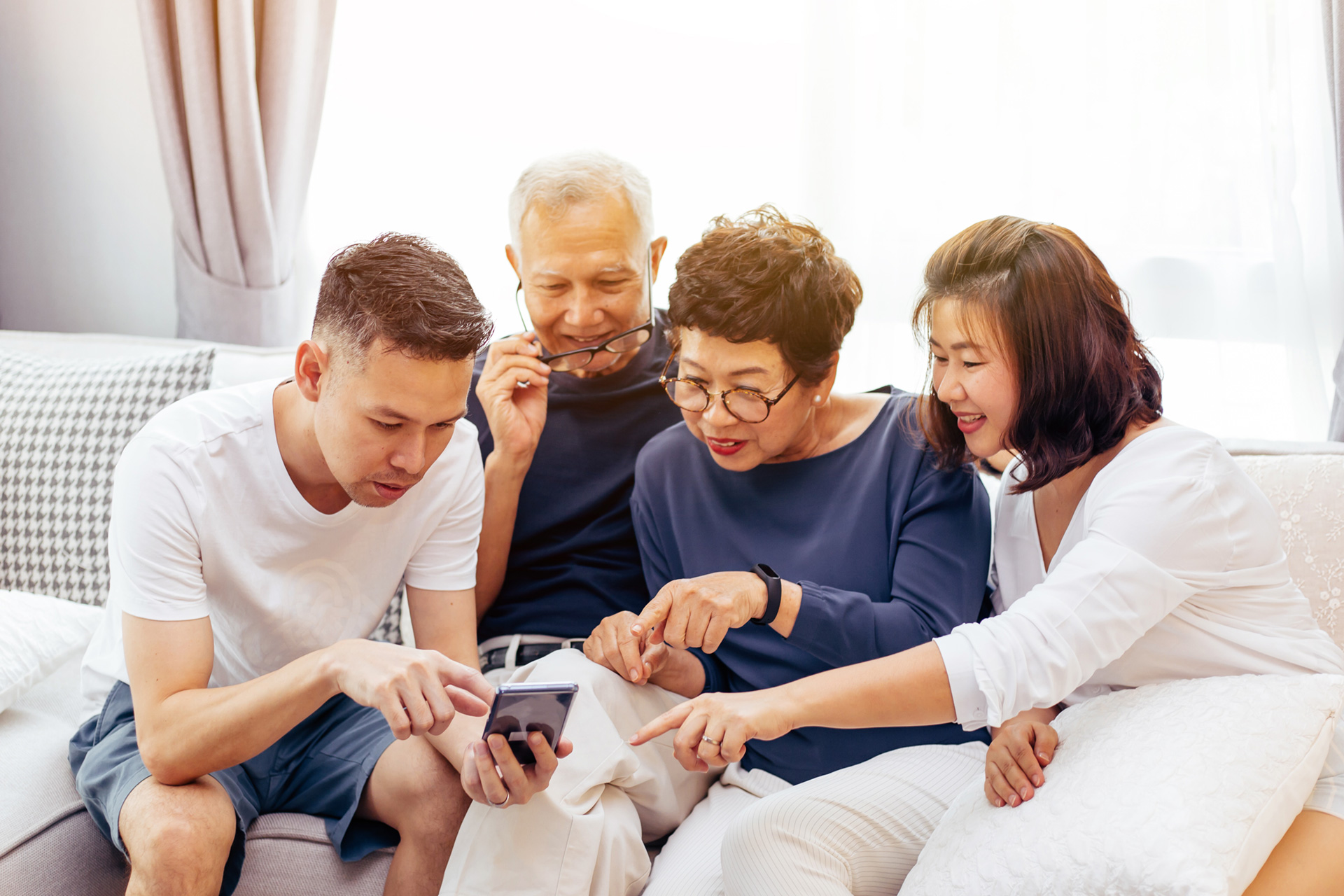 A family smiling and discussing something on a mobile screen