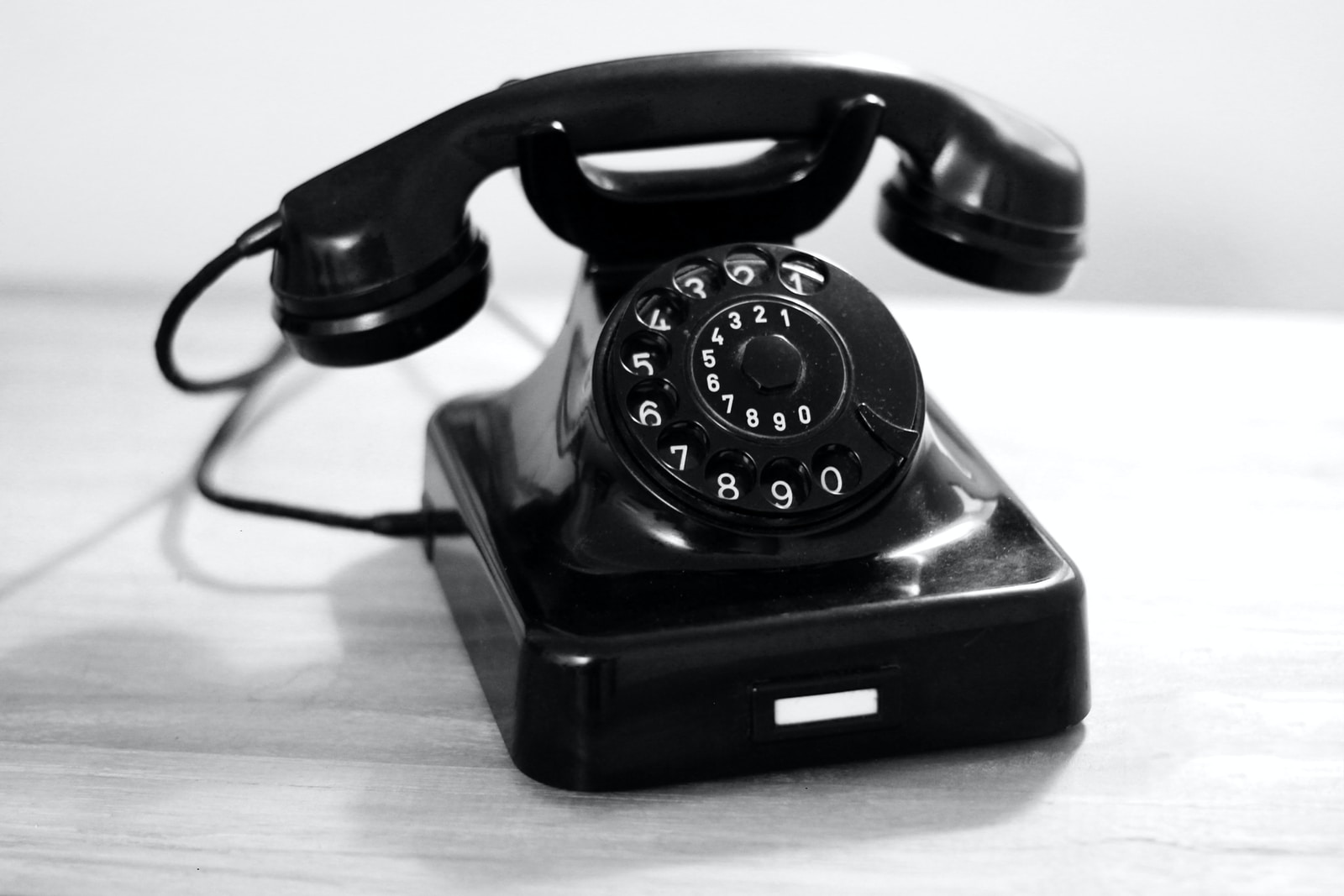 black rotary phone on white table